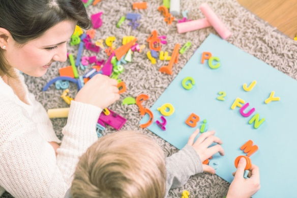 Young boy learning letters during a session with speech therapist